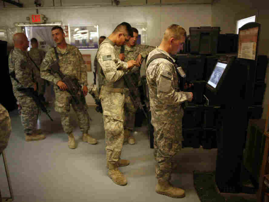 Soldiers withdraw cash from an ATM at Kandahar Airfield, Afghanistan, Sunday, Aug. 1, 2010.