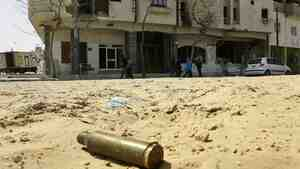 Libyans walk along a street close to Martyr's Square in the city of Zawiya, west of the capital, Tripoli, on Tuesday. During the first few weeks of the uprising, Zawiya was one of the most contested cities. Now, the rebellion here has been crushed.