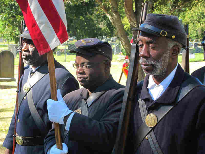 Civil War re-enactors representing the 54th  Massachusetts Volunteer Infantry dedicate a  gravestone for a black Civil War veteran in Charleston, S.C., in November 2010.