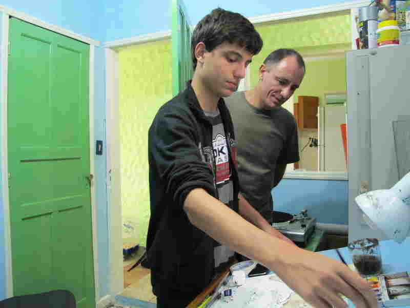 Joao Montanaro works on a cartoon in his studio with his father, Mario  Barbosa. He says his fascination with cartoons began when his dad showed him several anthologies featuring Brazil's best cartoonists when he was younger.