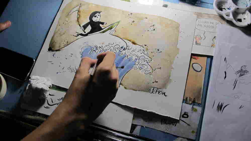 Joao Montanaro works on a cartoon illustrating the devastation the tsunami brought to Japan.