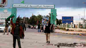 Brandishing an image of Libyan leader Moammar Gadhafi, forces celebrated after retaking the eastern Libyan oil town of Ras Lanuf on March 12 from rebel forces fighting to topple the regime.