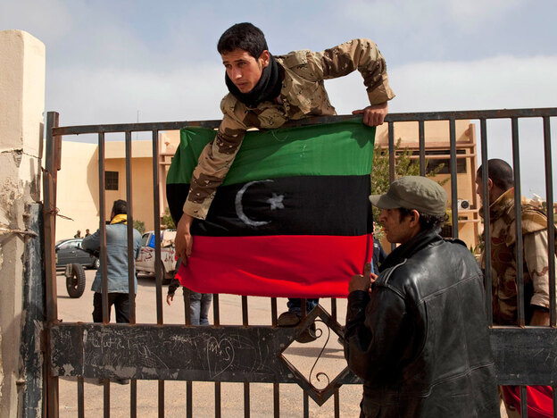 Libyan rebels who are part of the forces fighting against leader Moammar Gadhafi put a pre-Gadhafi Libyan flag on the gate of a government building in the town of Ras Lanuf, eastern Libya, on March 5.