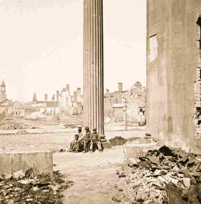 Four freed African-American children sit amid the ruins of Charleston, S.C., in 1865.