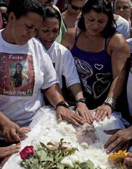 Relatives mourn over the body of 14-year-old Luiza Paula da Silveira Machado.