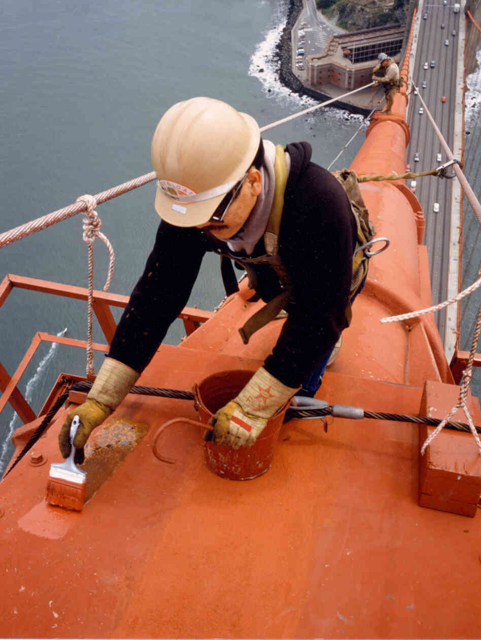 A painter touches up one of the bridge's cables. When it came time to decide the paint color for the bridge, consulting architect Irving Morrow wanted a warm hue to contrast with the cool grays, blues and greens of San Francisco Bay.