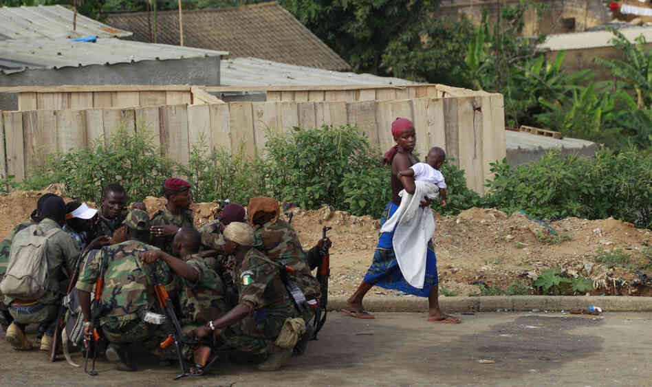 An Abidjan woman passes fighters loyal to Alassane Ouattara as they share a morning meal on Friday, April 8, 2011.
