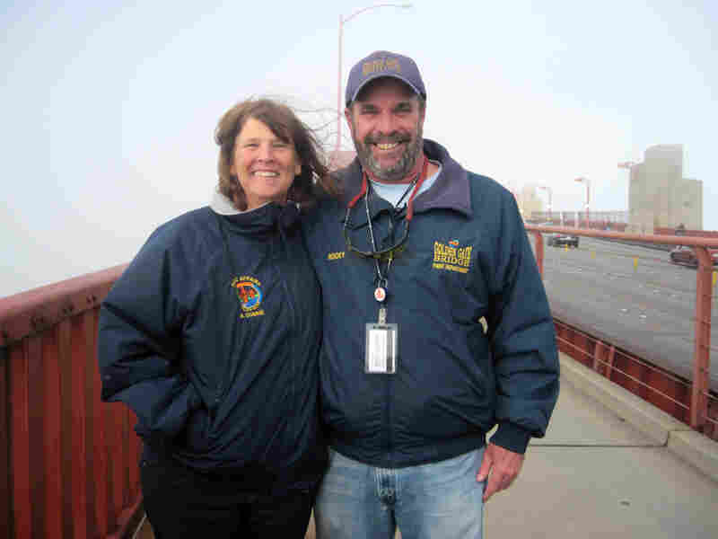 Golden Gate Bridge spokeswoman Mary Currie and paint superintendent Rocky Dellarocca stand on the bridge. The orange cables behind them are obscured by thick fog. From July to October, foghorns blare for more than 5 hours a day on average.