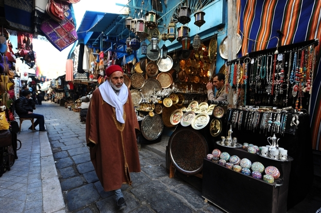 "A Tunisian man walks by craft shops in the medina in February. Today, the shops are suffering for lack of tourists. ""The tourism is catastrophic in Tunis today,"" says Said Ayari, who sells handicrafts like traditional pointed leather shoes."