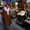 """A Tunisian man walks through a medina in February. Today, the shops are suffering for lack of tourists. """"The tourism is catastrophic in Tunis today,"""" says Said Ayari, who sells handicrafts like traditional pointed leather shoes."""