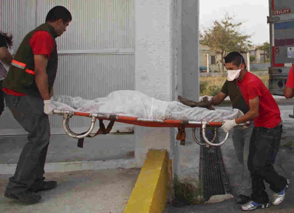 Workers move a body from a refrigerated truck into the local morgue in Matamoros, Mexico, after victims were discovered in several mass graves.