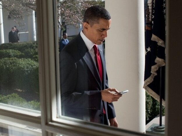 President Barack Obama checks his BlackBerry as he walks along the Colonnade to the Oval Office, March 18, 2010.