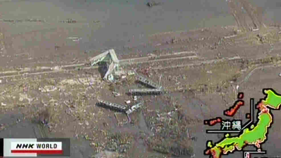 A screen grab taken from news footage by Japanese public broadcaster NHK shows an aerial view of damaged train carriages in Shinchi, Fukushima prefecture, on March 12.