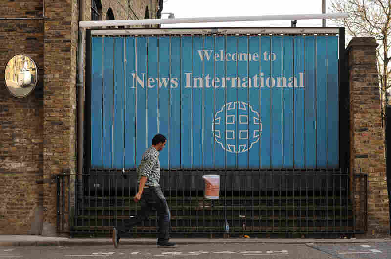 A man walks past the entrance to News International Ltd. in London on Friday. The company is apologizing to politicians and celebrities who were victims of a phone-hacking scheme at the company's tabloid News of the World.