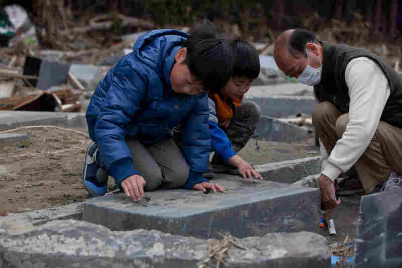 Ren Sato, 9, removes sand from a damaged family grave in Ishinomaki, Miyagi prefecture.