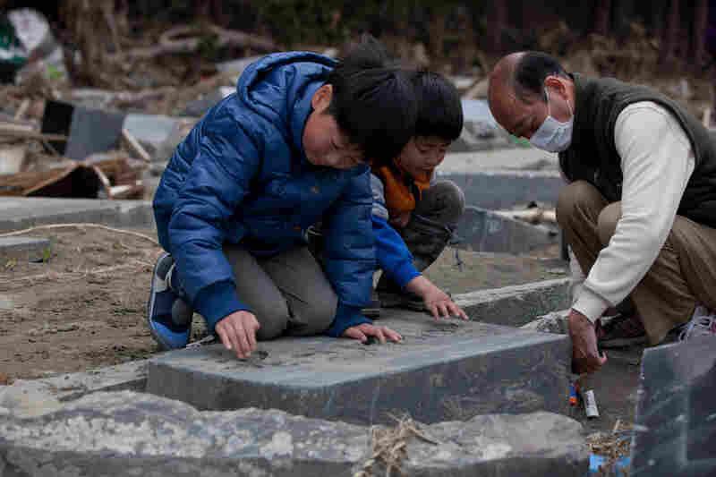 Ren Sato, 9, removes sand from a damaged family grave in Ishinomaki, Miyagi prefecture.