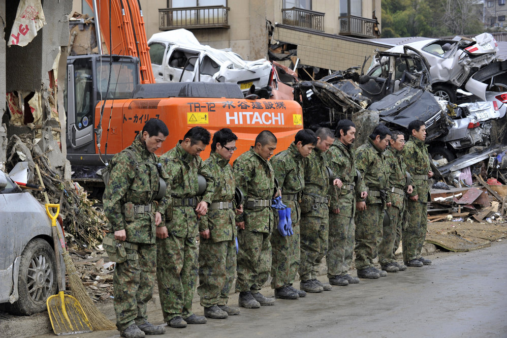 Members of the Japanese military offer a silent prayer for the dead in Kesennuma, Miyagi prefecture.