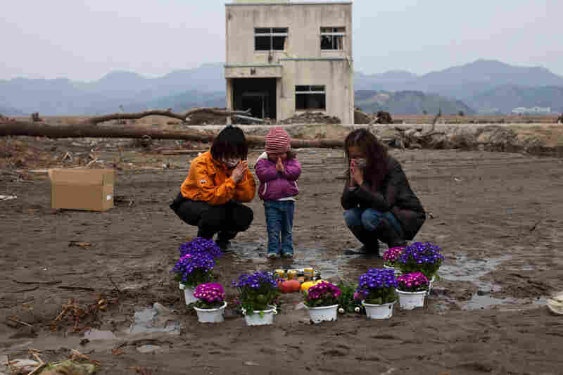 Two-year-old Ayaka (center) and family members pray for her missing grandmother and great-grandmother at a vacant lot where they lived in Ishinomaki, Miyagi prefecture.