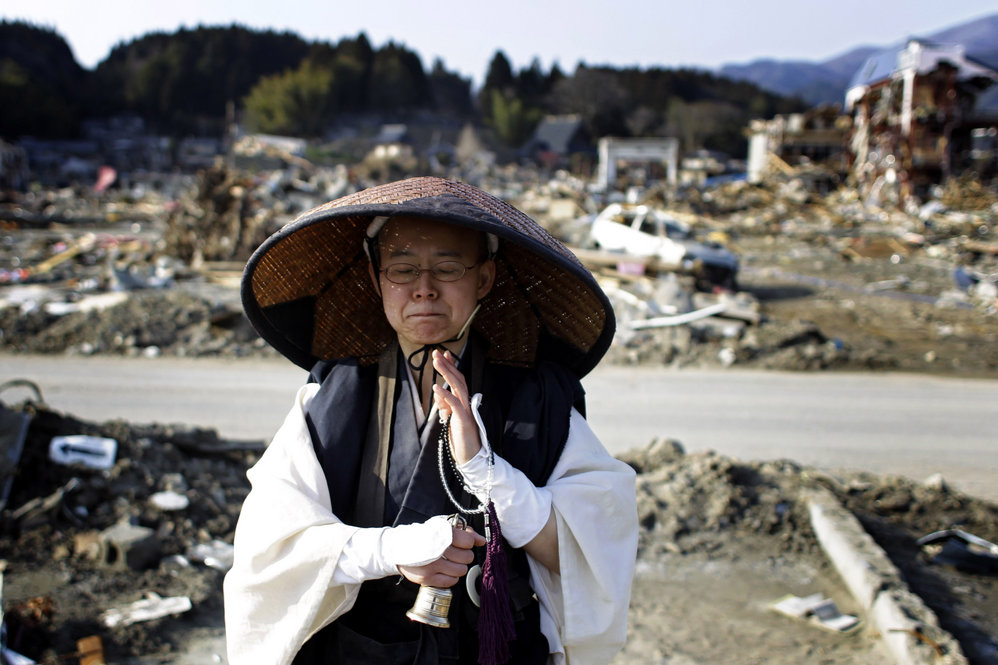 A Japanese Buddhist monk prays at an area devastated by the earthquake and tsunami in Rikuzentakata, Iwate prefecture on Sunday.