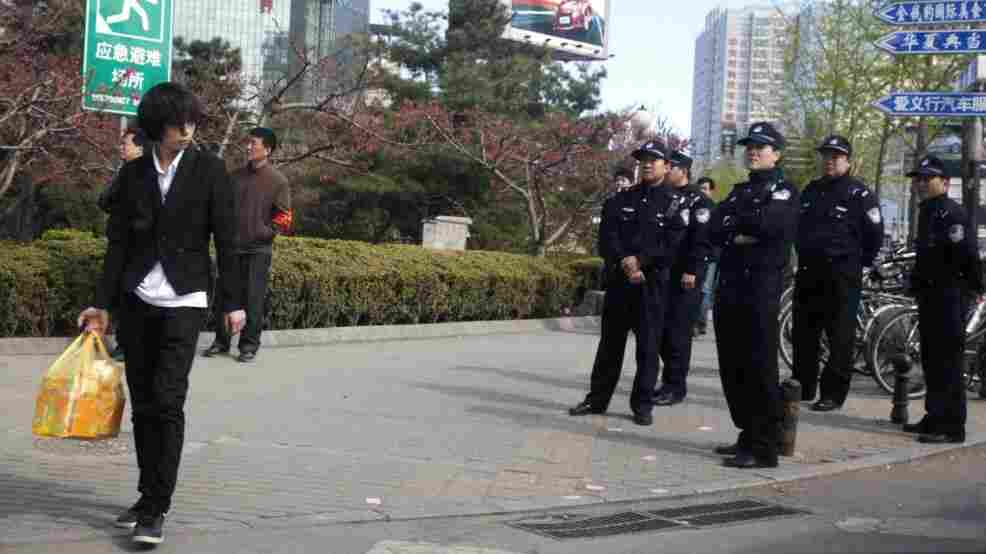 Chinese police officers watch an area near a building that leaders of the unregistered Shouwang house church had told parishioners to gather in Beijing, China, Sunday, April 10, 2011.