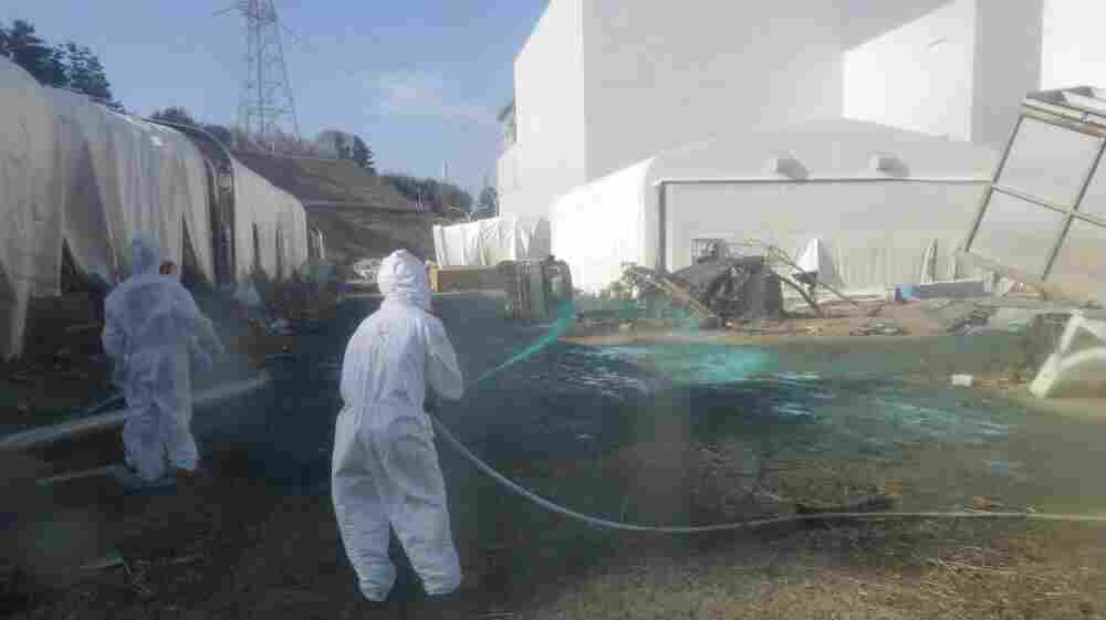 Workers at the Fukushima Dai-ichi nuclear power plant spray a substance to help reduce dust on April 1. The cleanup operation at the facility could take more than a decade.