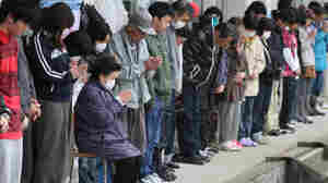 Evacuees offer silent prayers for quake and tsunami victims at a shelter in Minamisanriku, Miyagi prefecture on April 11, 2011.
