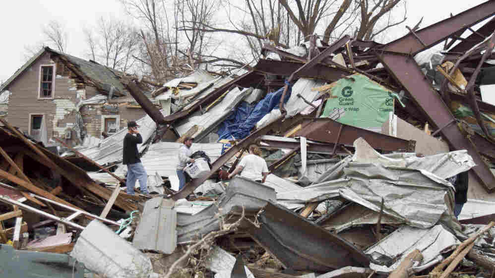 Jason Mauch, center, carried a basket of belonging from his destroyed house in Mapleton, Iowa, on Sunday (April 10, 2011).