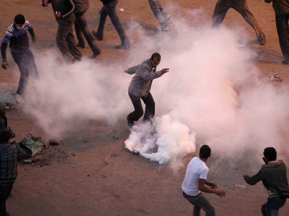 During clashes in Suez on Jan. 27, Egyptian demonstrators demanding the ouster of President Hosni Mubarak try to remove a tear gas canister thrown by anti-riot police.