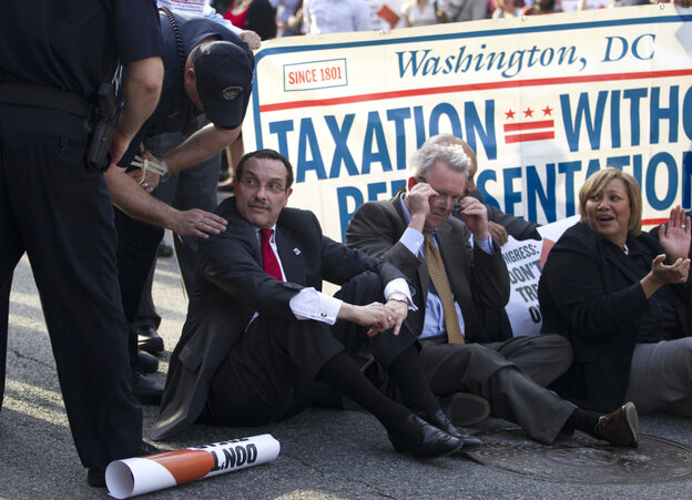 A Capitol Hill police officer talks to Washington Mayor Vincent Gray before he was arrested during a protest on Capitol Hill.