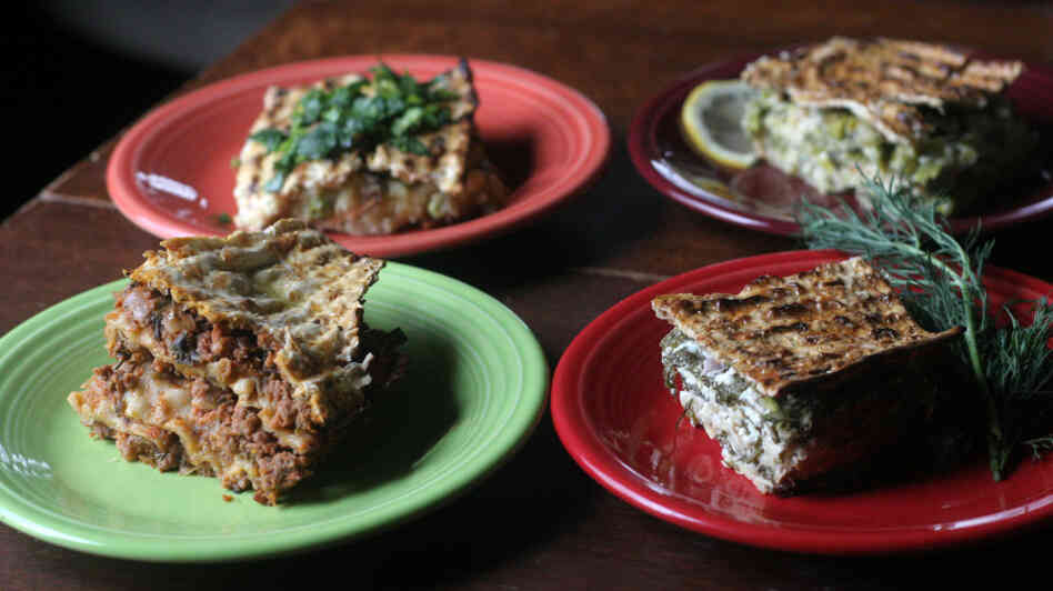 Four plates with slices of a variety of minas, or layered matzo pies (clockwise from upper left): Roman-Inspired Potato, Pea And Artichoke Mina With Gremolata; Leek And Asparagus Mina With Mint And Lemon; Spinach And Feta Mina With Fresh Dill; and Mina De Carne.