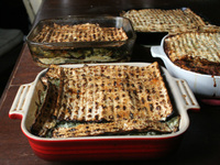 Layered matzo pies, or minas, await slicing. The top layer of matzo is glazed with a beaten egg, to give the finished dish a burnished shine.