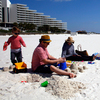 A family from New Orleans visits a beach in Pensacola, Fla., just before spring break season last month. In the distance, workers continue to clean up after the Deepwater Horizon oil spill.