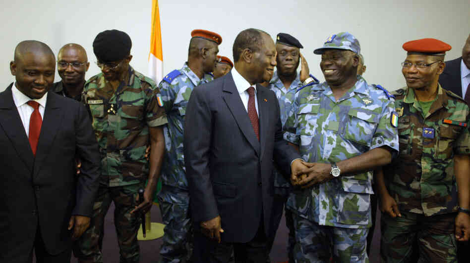 Ivory Coast's President Alassane Ouattara chats with military and police officials who've now pledged their support to him.