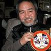 Ken Terui, proprietor of Johnny's Jazz Cafe, shows off a tin of fruitcake sent to him by pianist Toshiko Akiyoshi.
