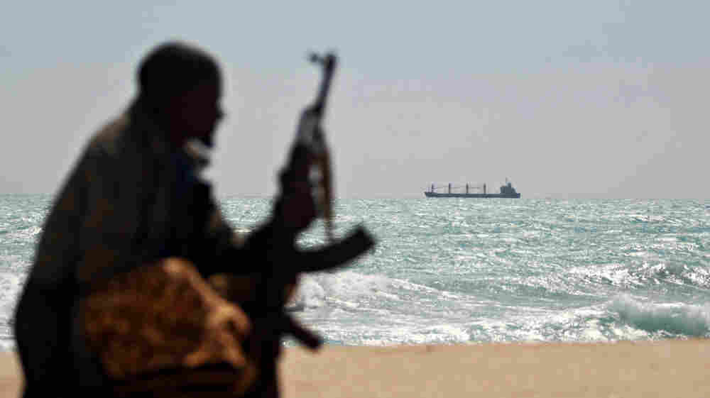 An armed Somali pirate keeps vigil along the coastline of Hobyo, a pirate lair on the Indian Ocean.