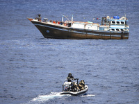 In this photo released by the Dutch defense ministry, suspected pirates stand on deck with their hands raised as Dutch marines approach a hijacked Iranian fishing boat off the coast of Somalia on April 4.