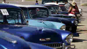 A woman looks at old cars parked in front the National hotel during a classic car rally in Havana, Cuba, April 7.