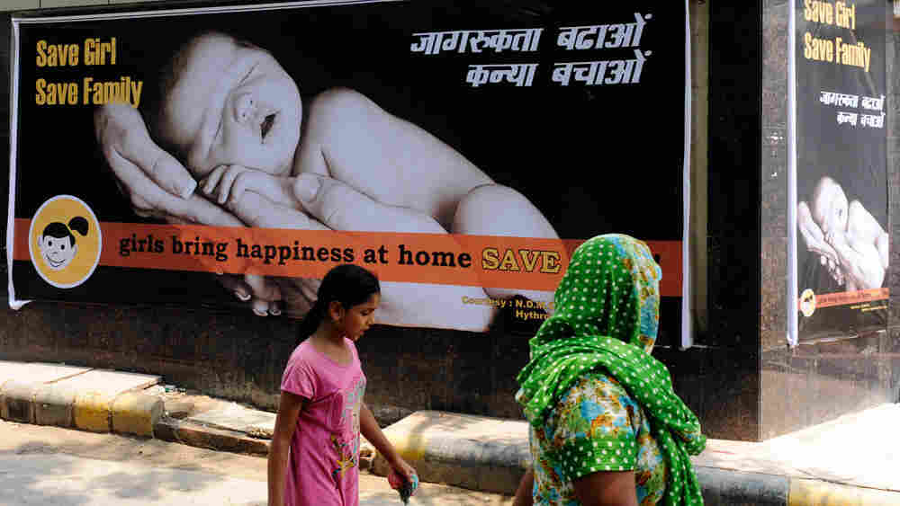 A woman and child walk past a billboard that promotes having girls last July. In India, there are far fewer girls born each year than boys. Some families use ultrasound technology to determine the gender of fetuses and then abort the females.