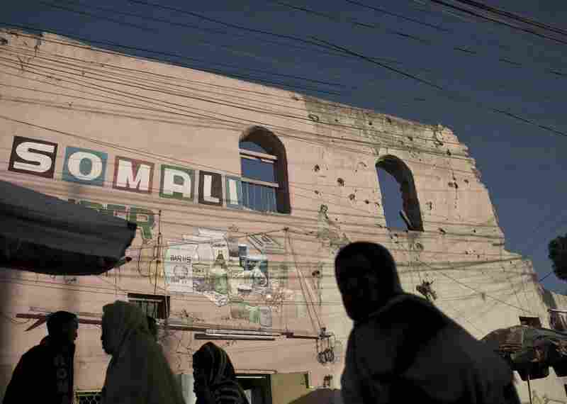 Men and women walk through the bustling central market in Hargeisa, passing war-damaged buildings.