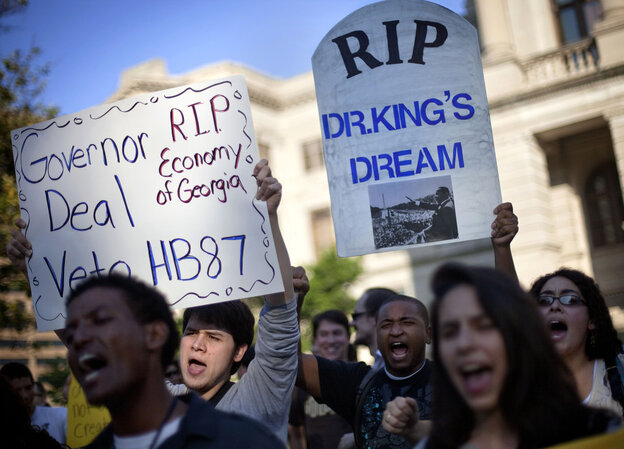 Jason Azurmendi, left, is joined by Will Pesante, center, and Kristen Everett, right, all of Atlanta, as they protest a controversial immigration bill outside the state Capitol Thursday.