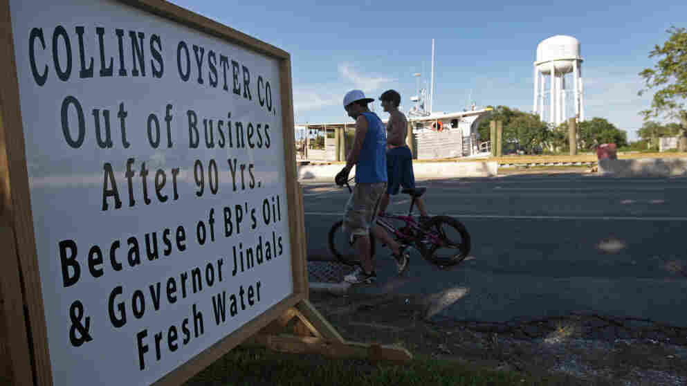Teens walk past a closed oyster business last week in Golden Meadow, La. A number of Louisiana fishermen have had to close because of economic conditions blamed on the Deepwater Horizon oil spill. Nearly a year after the spill, hundreds of lawsuits are slowly moving through the courts.
