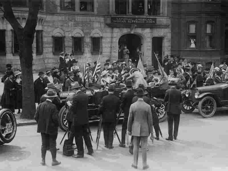 A crowd gathers around the car that will take Jeannette Rankin, the first female member of Congress, to be sworn in in 1917.