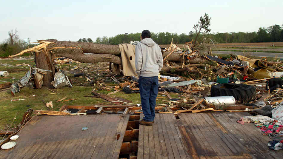 Clifton Perry stands on what's left of this home Monday in Colerain, N.C., where a tornado hit Saturday.