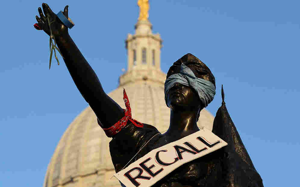 """A sign that reads """"recall"""" hangs on a statue in front of the Wisconsin state Capitol last month in Madison. In the state Senate, as many as 16 senators — Republicans and Democrats alike — could face recall elections this year."""