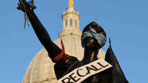 "A sign that reads ""recall"" hangs on a statue in front of the Wisconsin state Capitol last month in Madison. In the state Senate, as many as 16 senators — Republicans and Democrats alike — could face recall elections this year."