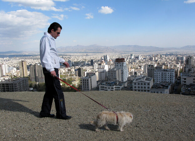 An Iranian man walks with his dog while spending a weekend holiday in Tochal north of Tehran, Iran.