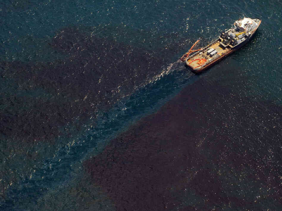 A support ship over the site of the BP Deepwater Horizon oil well transitions through a sheen of oil as workers try to stem the flow of the spill off the coast of Louisiana last June. Wednesday marks the one-year anniversary of the oil spill.