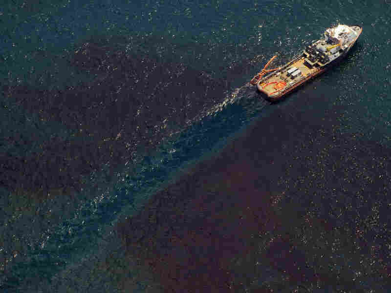 A support ship over the site of the BP Deepwater Horizon oil well transitions through a sheen of oil as workers try to stem the flow of the spill off the coa