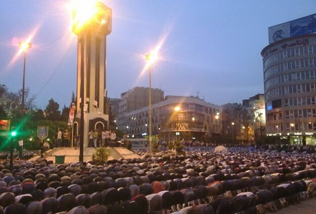 A cell phone photo taken Monday shows Syrians kneeling in prayer in Clock Square in the city of Homs. A day later, security forces fired tear gas and live ammunition at hundreds of anti-government protesters there.
