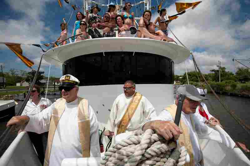 "The Blessing of the Fleet takes place in several Catholic fishing communities in southern Louisiana to mark the start of the shrimping season. Priests float down the bayou, praying for the community's shrimping vessels as they pass by. Here, Monsignor Frederic Brunet, (left), Deacon Gary Lapeyrouse and the Rev. Brendan Foley ride aboard the ""Maycie Brooke"" during the ceremony in Chauvin, La."